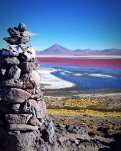 pink lagoon with rocks and flamingos and mountains in bolivian lagoons