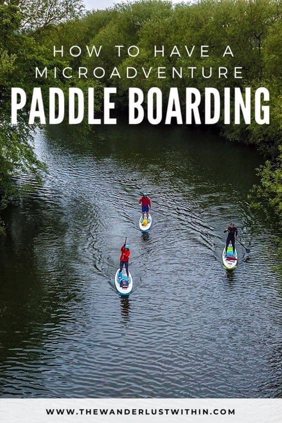 aerial view of 3 people paddle boarding along a river lined with trees in bedfordshire on a microadventure in the uk