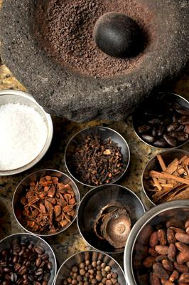 spices and ingredients for traditional food from ecuador sit in pots with a pestle and mortar