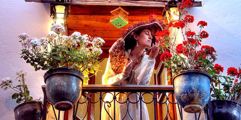 women in hat smelling flowers on her balcony in la ronda in quito in ecuador
