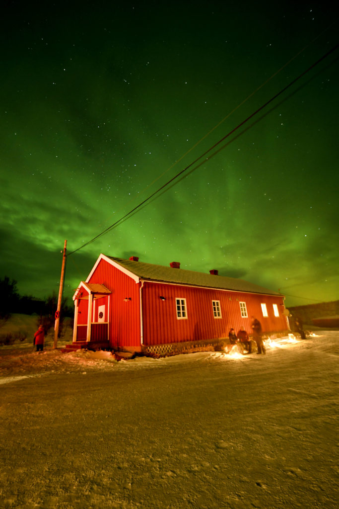 A red Norwegian building with northern lights above them in Arctic Norway