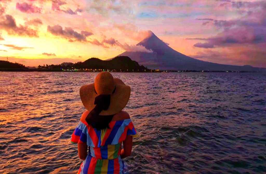 girl in stripey dress looking at mayon volcano under a pink sunset in legazpi philippines