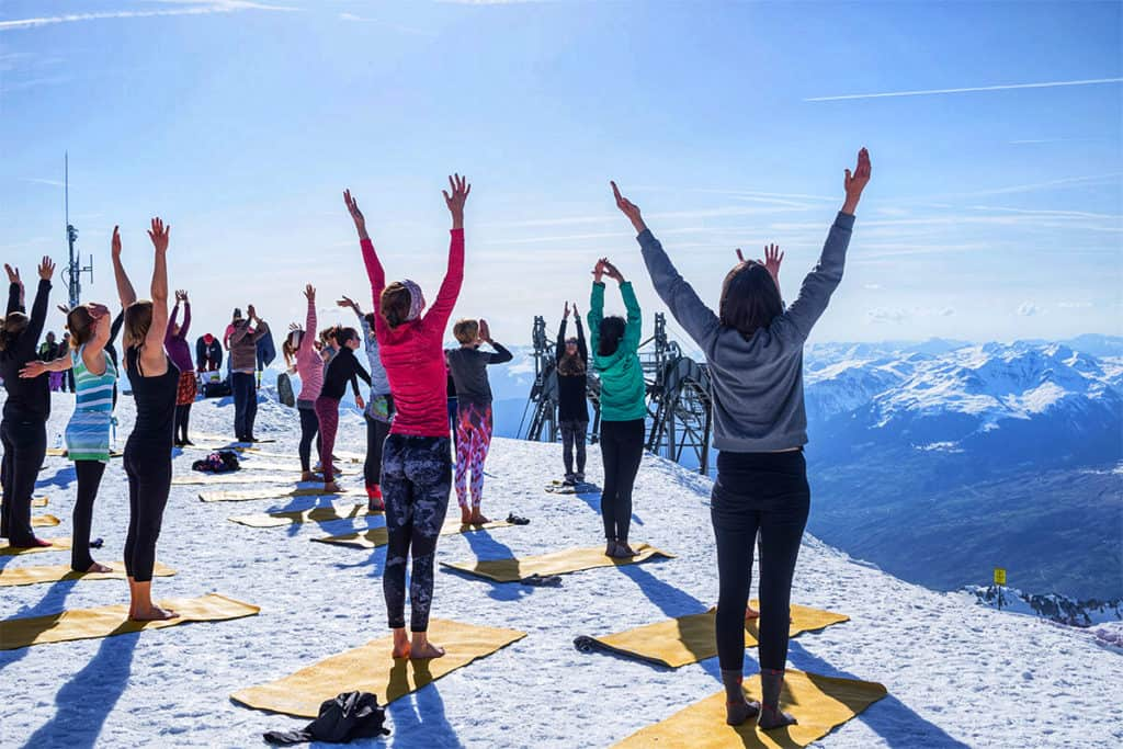 mountain yoga class taking part with lots of attendees at aiguille rouge in Les Arcs France