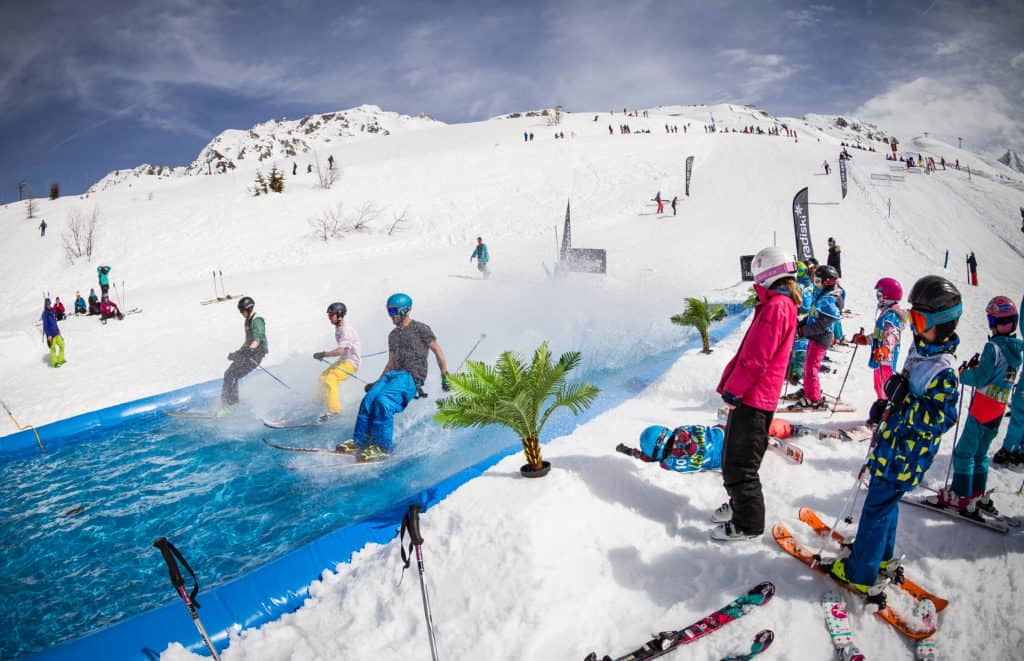 several skiers ski down an inflatable water slide in the middle of ski slope, getting very wet with onlookers in Les Arcs France