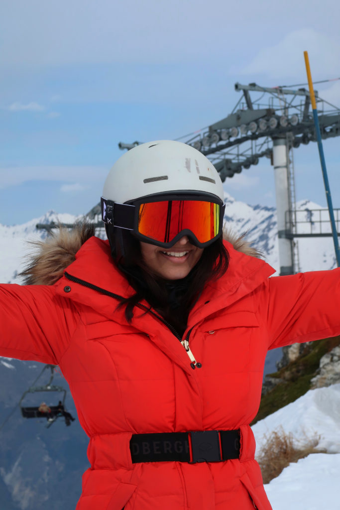 girl in red ski jacket, white helmet and red goggles smiling with arms in air on the ski slopes in Les Arcs France