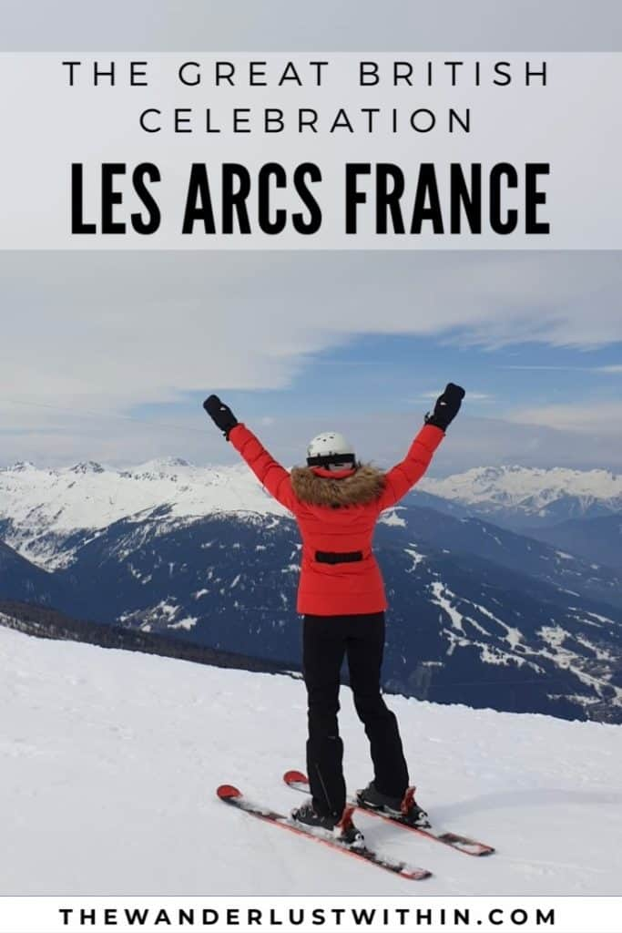 girl in red ski jacket has arms in air on ski slop with mountains behind in les arcs france