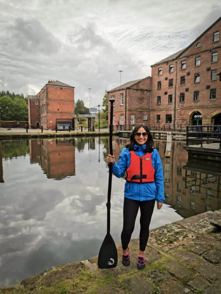 Girl in life jacket with paddle by canal