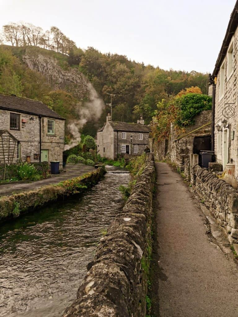 a small lane with stone houses surrounded by trees and autumn colours. there is a river running through the village of castleton in the peak district