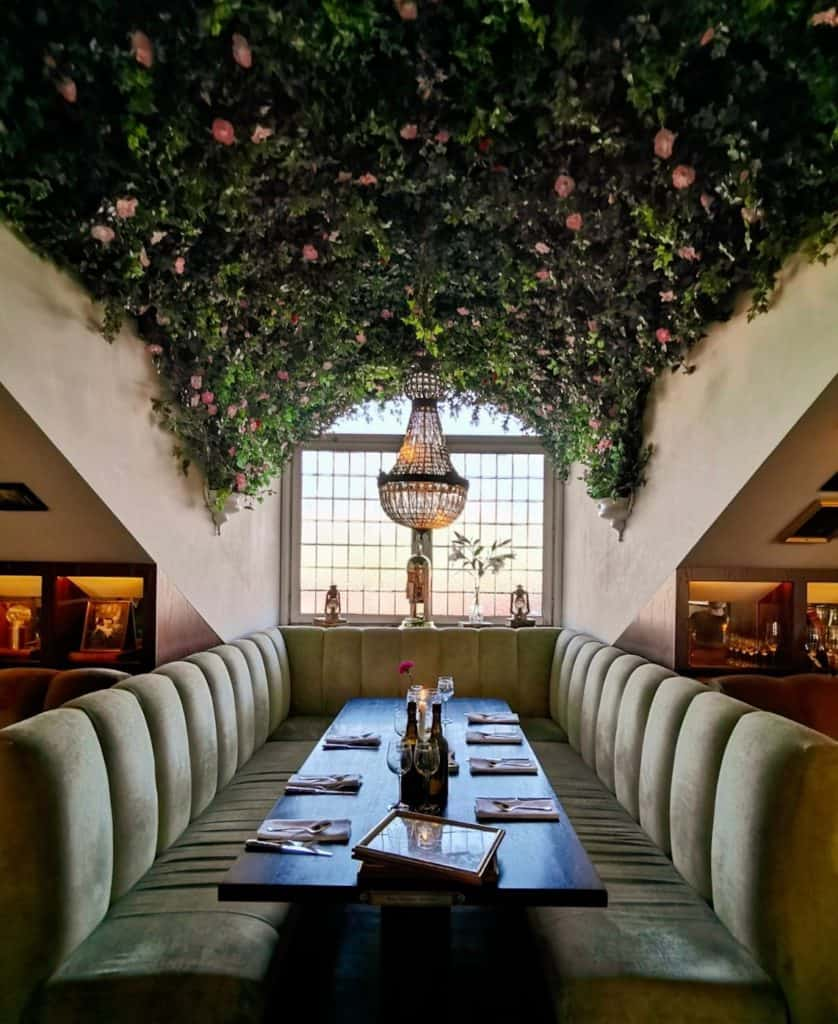 interior of atelier restaurant in Gothenburg. ceiling is covered in flowers with large window seats