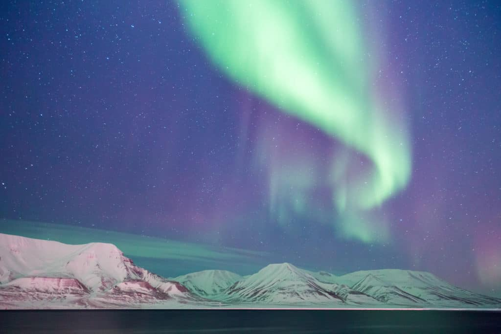 green swirl of northern lights in the sky with purple and blue sky and stars visible. there are white snow capped mountains below in Alta Norway in winter