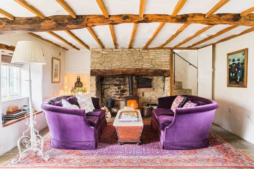 Asphodel Cottage with purple sofas and beams on ceilings. cotswolds airbnb