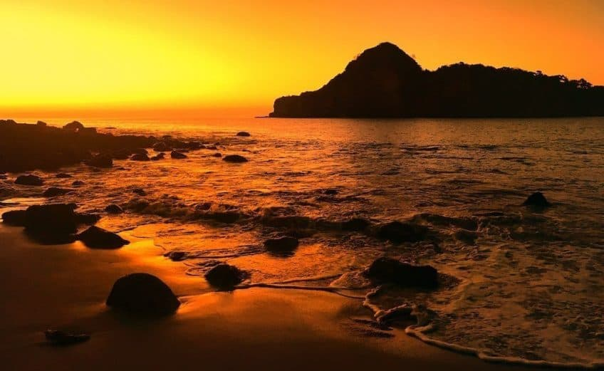 deep orange sunset on a beach with rocks and waves and the silhouette of an island in the near distance, it is redonda bay, one of the best beaches in Nicaragua