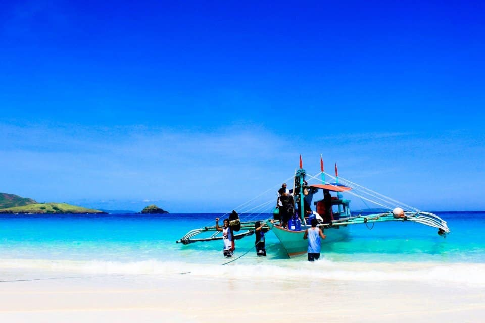 outrigger boat in philippines has many people boarding it is on a white beach with bright blue water on calaguas islands best asian beaches