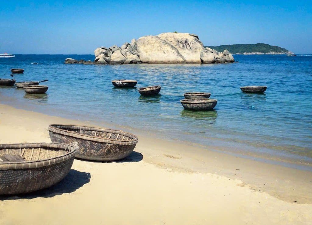 white sand beach and blue water with weaved baskets floating on the surface and sitting on the beach, they are one of the best things to do in the Cham islands in Vietnam near hoi an. one of the beautiful islands in asia