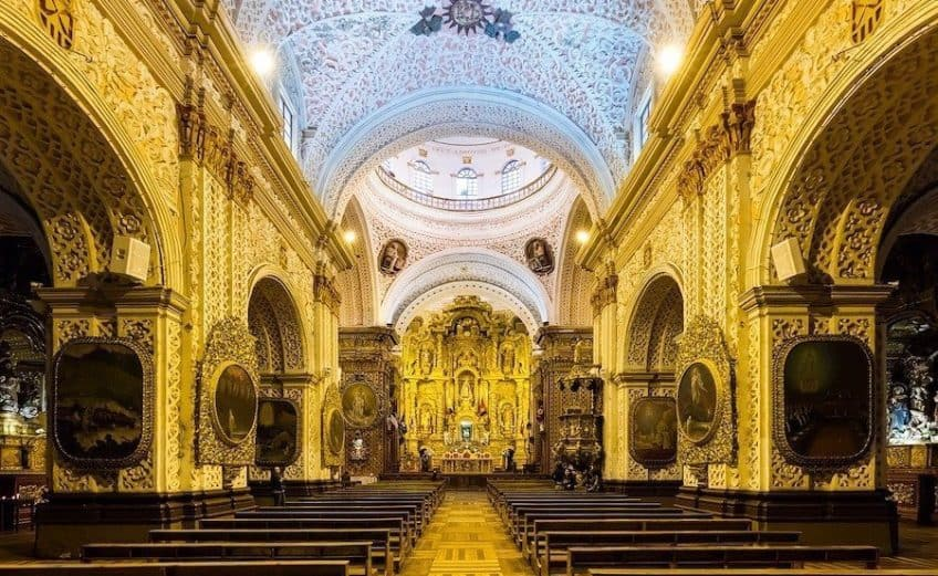 Inside of ornate gold decorated church in Quito Ecuador. the ceiling and walls are all covered in artwork and intricate carvings and it is one of the best places to visit in South America