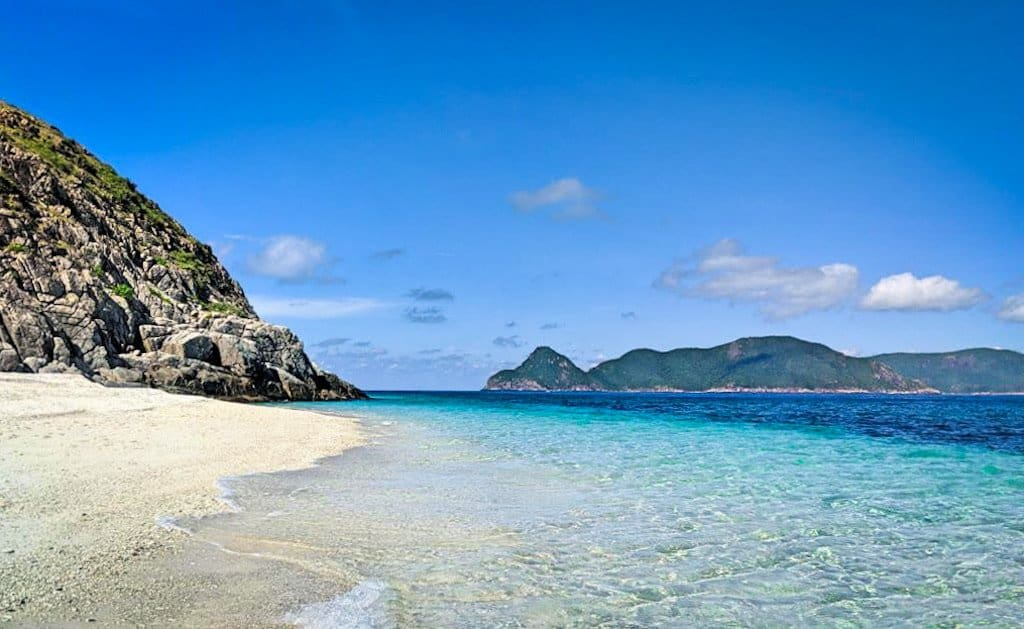 white sand beach and crystal clear blue waters with green and rocky islands in the background of con Dao islands a hidden gem in Vietnam and one of the most beautiful islands in Asia