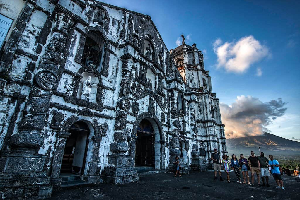 a white and old church in Legazpi Philippines next to an active volcano in Bicol.