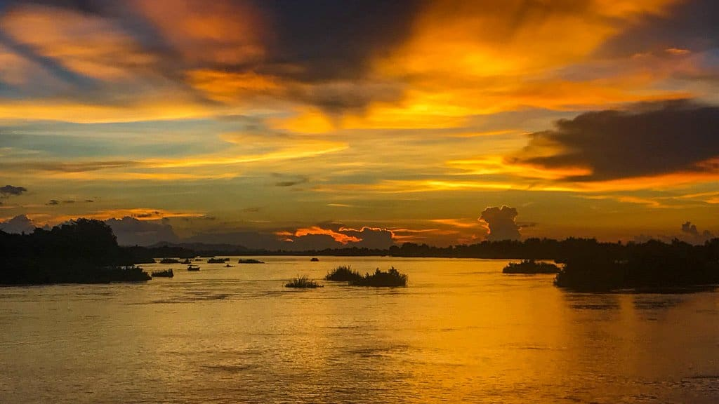 orange and yellow sunset with clouds over a river with silhouettes of islands in the water. it is Don Det island one of the 4000 islands in southern laos called si Phan don and are one of the most beautiful islands in asia