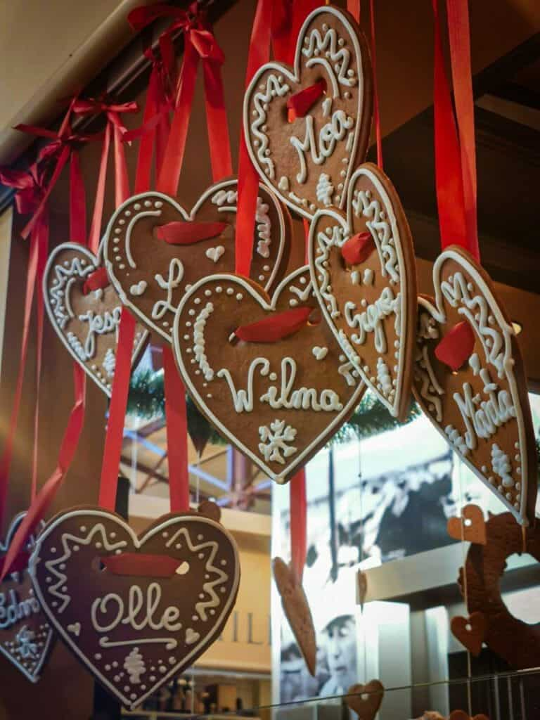 Several heart shaped decorated gingerbread cookies hang as decorations