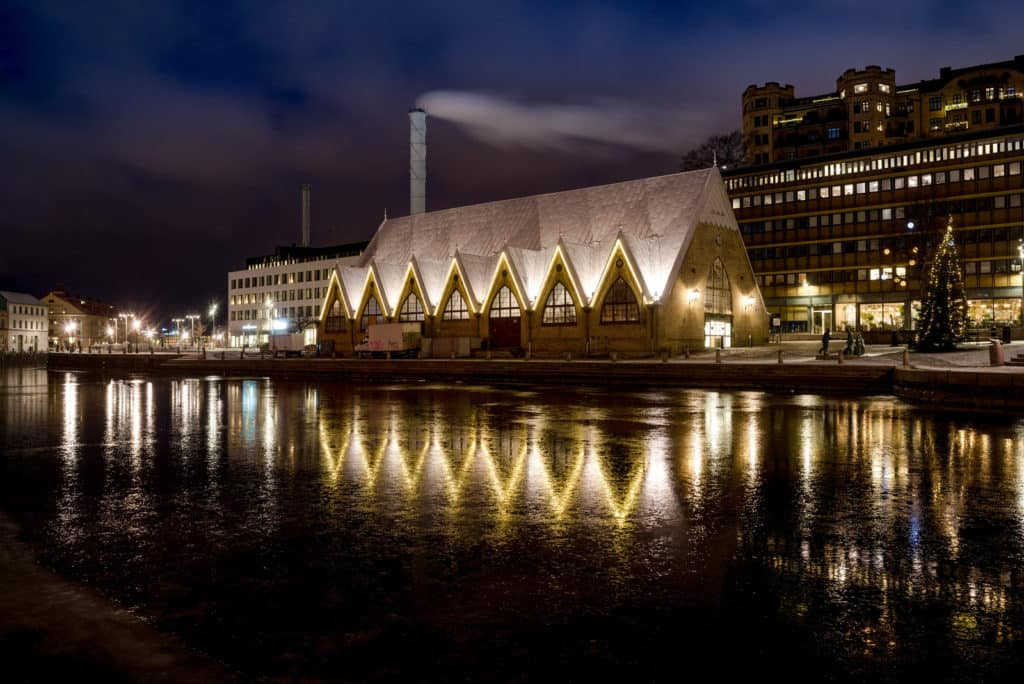 an industrial building with 7 sharp arches that make up the architecture, next to a canal with reflection in Gothenburg Sweden