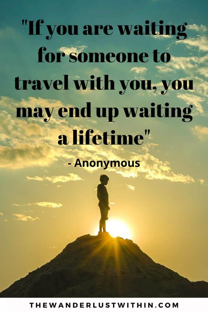 motivational inspirational solo travel quote saying If you are waiting for someone to travel with you, you may end up waiting a lifetime with a boy standing on top of mountain with blue and yellow sunset in background