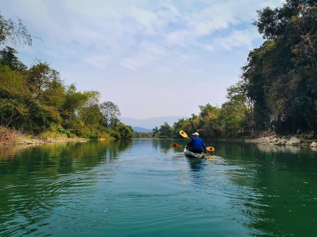 two people kayaking along the Nam Song river in Vang Vieng with the green water and quiet countryside, one of the great things to do in Vang Vieng