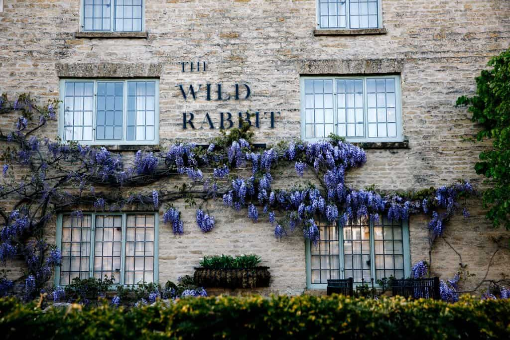 a building with purple wisteria growing on it and the words the white rabbit, a restaurant in kingham in the cotswolds