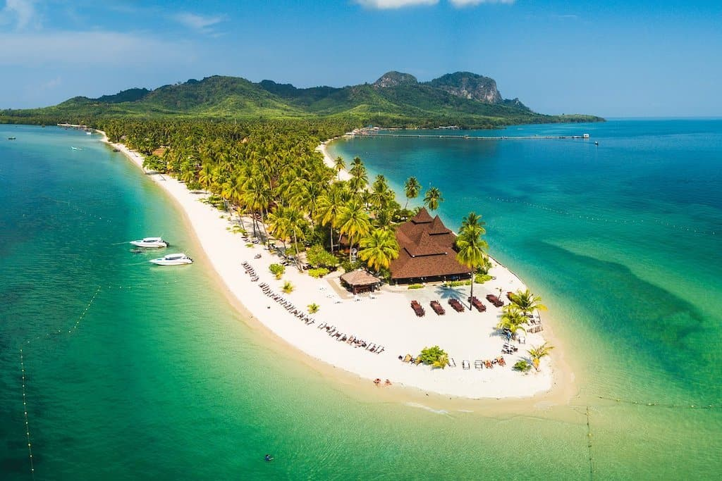 a white sand beach is covered in palm trees and in the shape of a finger it is surrounded by emerald green ocean and has a beach resort on the edge. it is one of the best asian islands in Thailand and Koh Mook