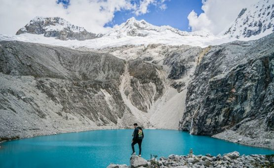 blue lake surrounded by white mountains and man standing in middle one of the best hikes in South America