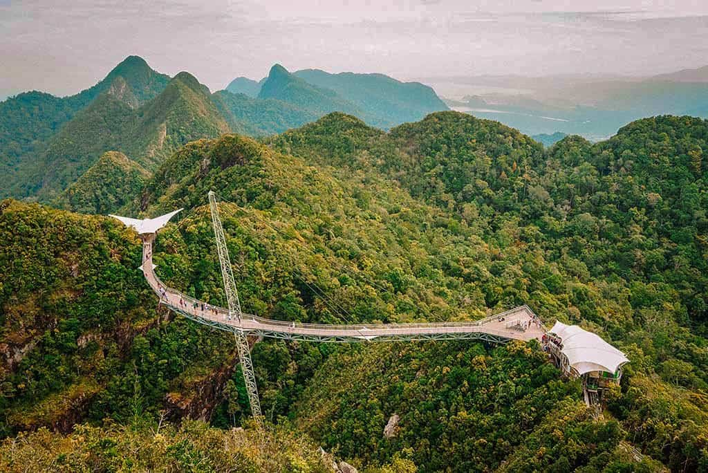 A view from above of a walkway bridge over the green forests and mountains of Langkawi island in Malaysia, one of the most beautiful islands in Asia