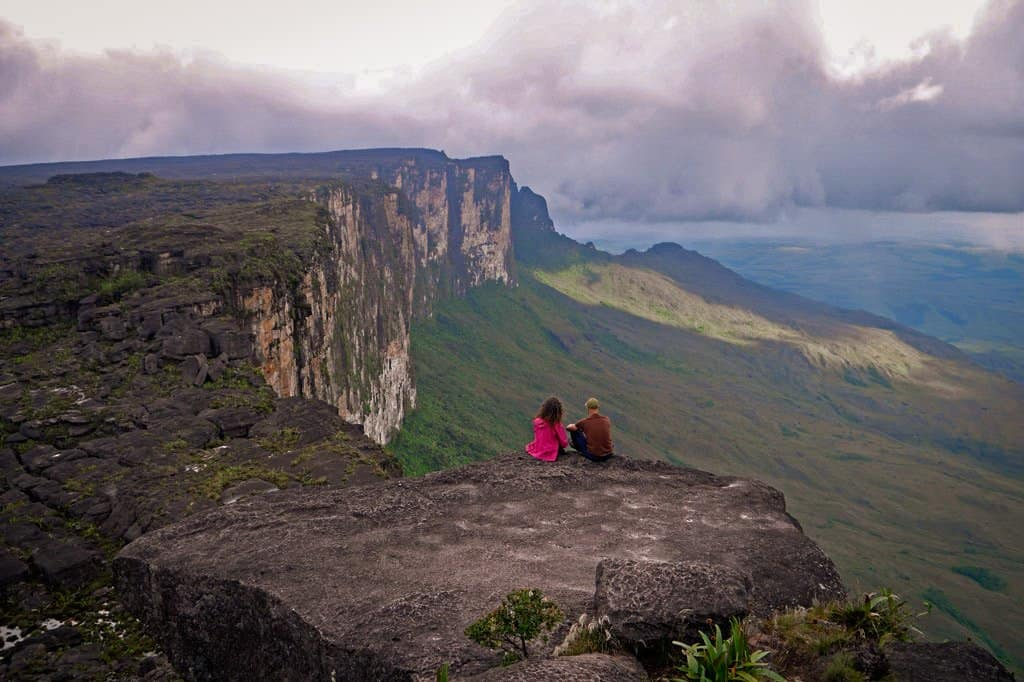 couple sit on edge of mountain in Venezuela called Mount Roraima, one of the best hikes in South America