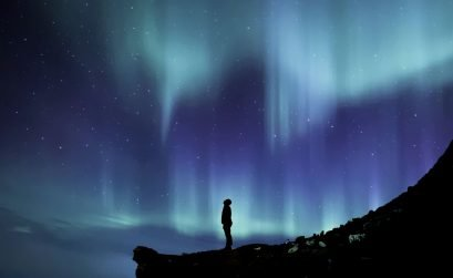 blue northern lights and stars in the sky with the silhouette of a man looking up into the sky