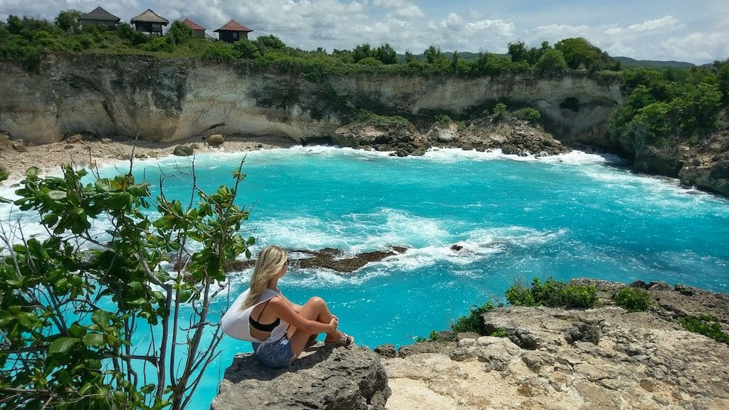 girl sits on rock and looks out onto a bright blue lagoon and cliffs in Nusa Ceningan near bali in Indonesia, one of the most beautiful islands in asia