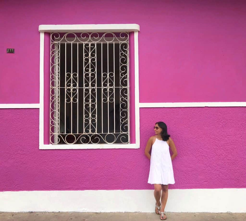 Girl wearing white dress standing infront of bright Pink building with window in Granada in Nicaragua