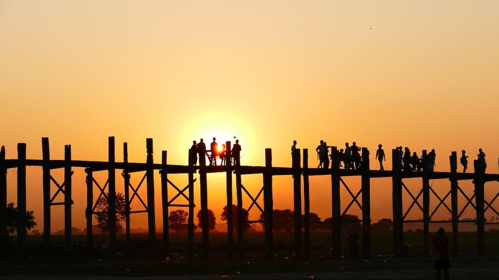 silhouettes of people crossing wooden bridge at sunset in mandalay in myanmar