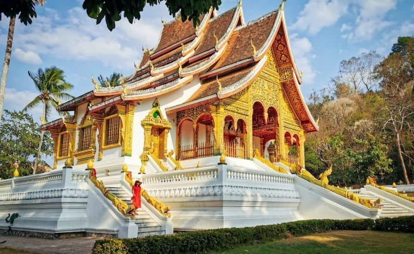 girl in red dress stands on steps of laos buddhist temple in luang prabang. covered in gold leaf and carvings the temple looks very ornate, and visiting it is one of the best things to do in luang prabang
