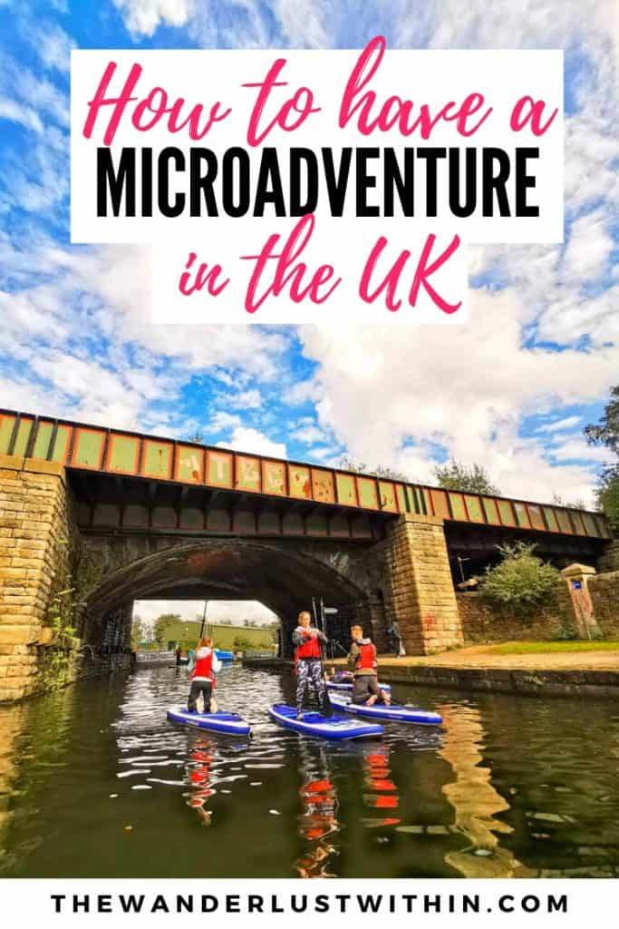 group of people stand up paddle boarding under a bridge in Sheffield taking part in a micro adventure in England