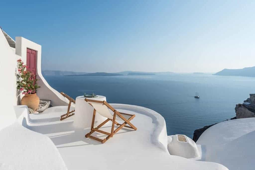 airbnb santorini oia with hot tub and outdoor seating area with views of sea
