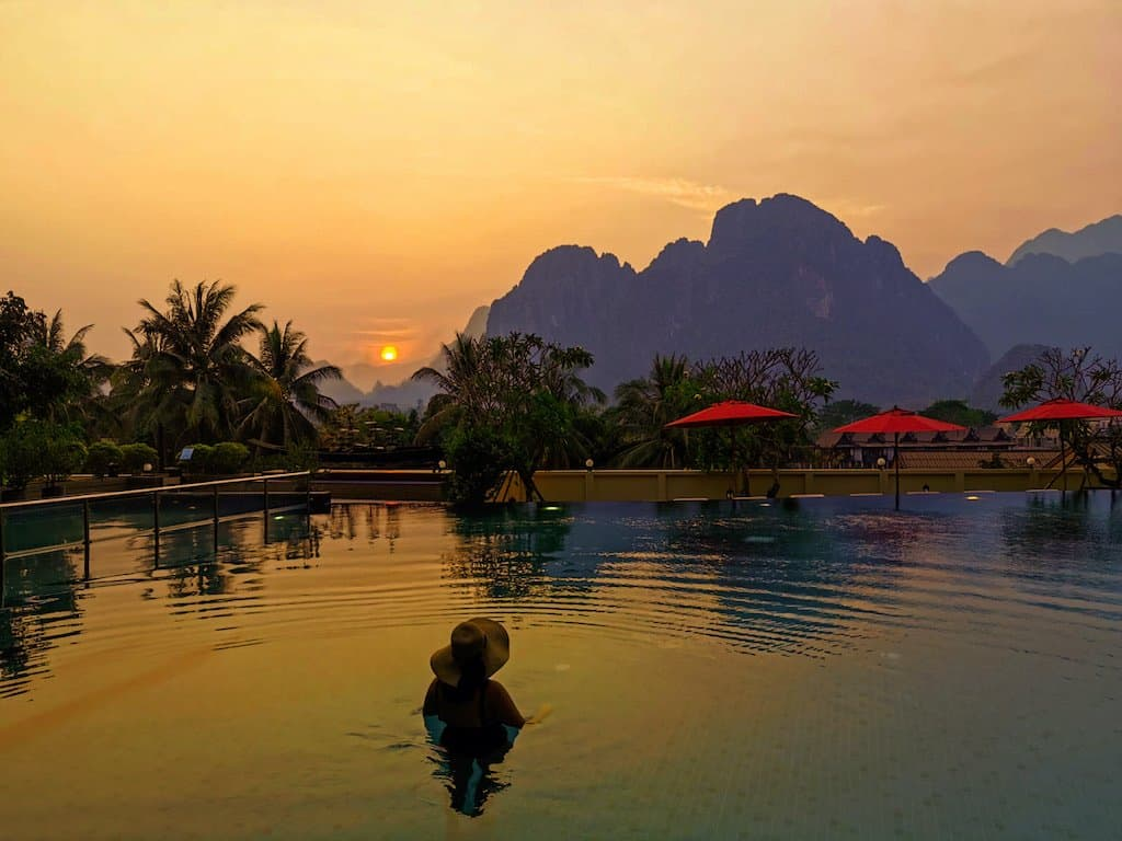 girl in pool with sunset view and mountains and palm trees in background in amari Vang Vieng Laos