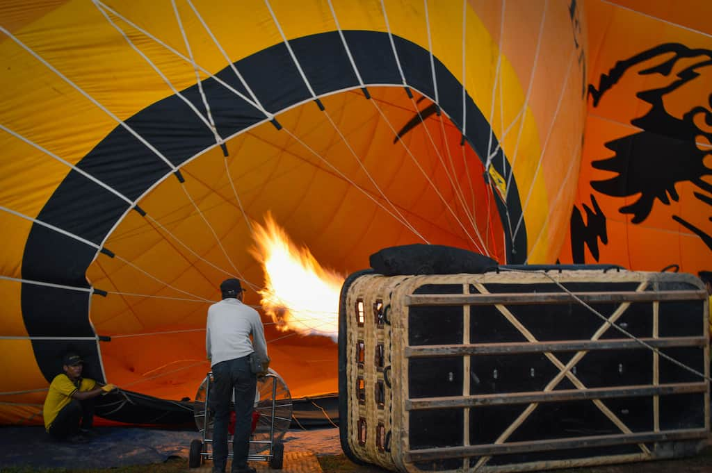 two men are inflating a yellow bagan hot air balloon before take off in myanmar