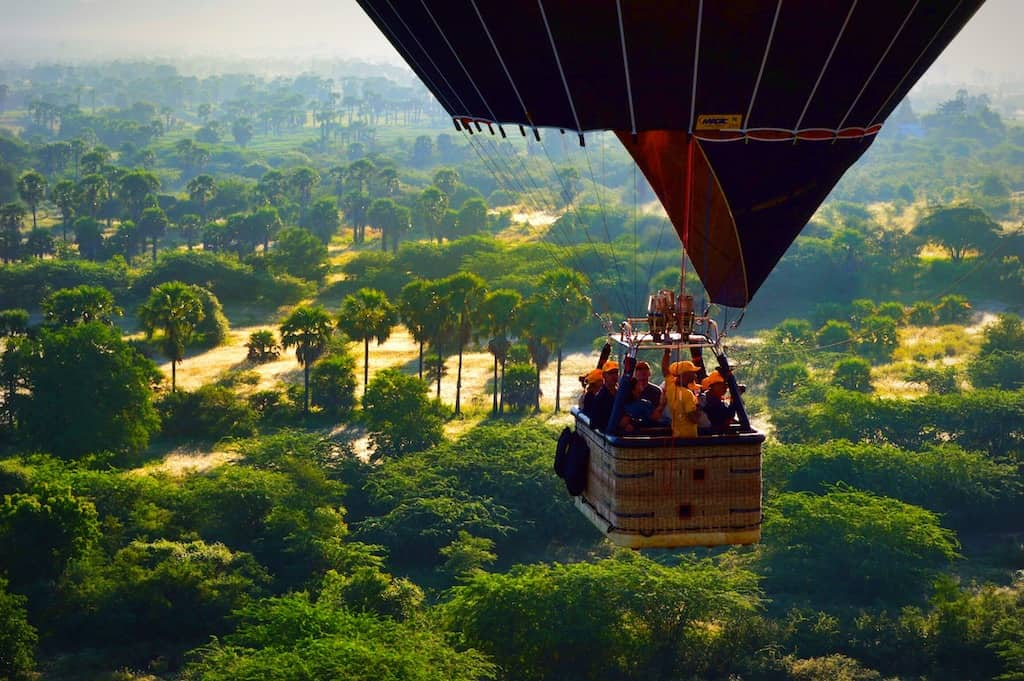close up view of people in hot air balloon wicker basket floating over lush green jungle like landscape in myanmar in a bagan hot air balloon