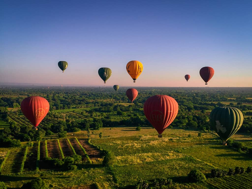 red yellow and green bagan hot air balloons are in the sunrise sky over green countryside in bagan