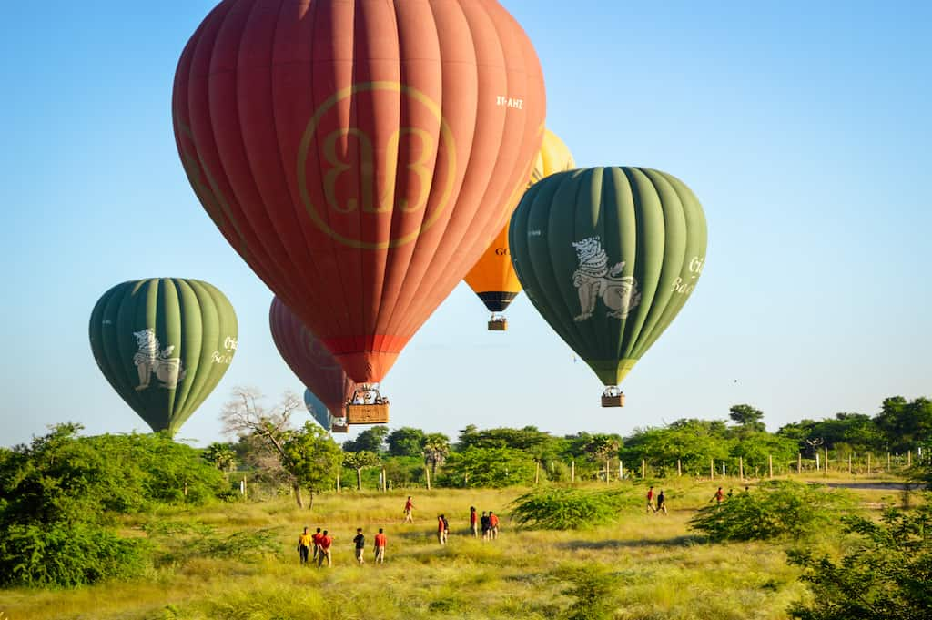 several hot air balloons are close to the ground and about the land on green grass with crew waiting to help in bagan myanmar