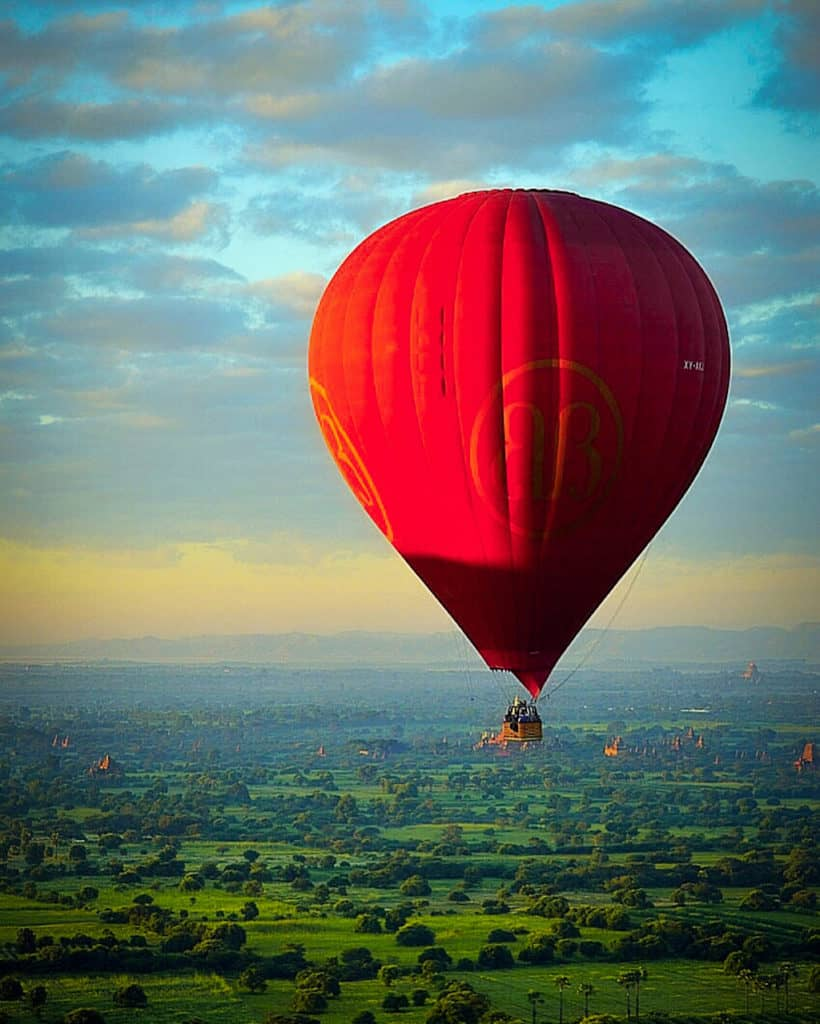 a red hot air balloon flies over a sunrise sky in bagan myanmar with green countryside and ancient buddhist temples below