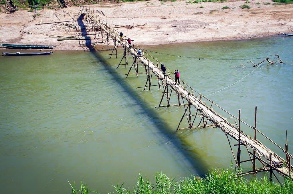 bamboo bridge over a green river in laos in luang prabang