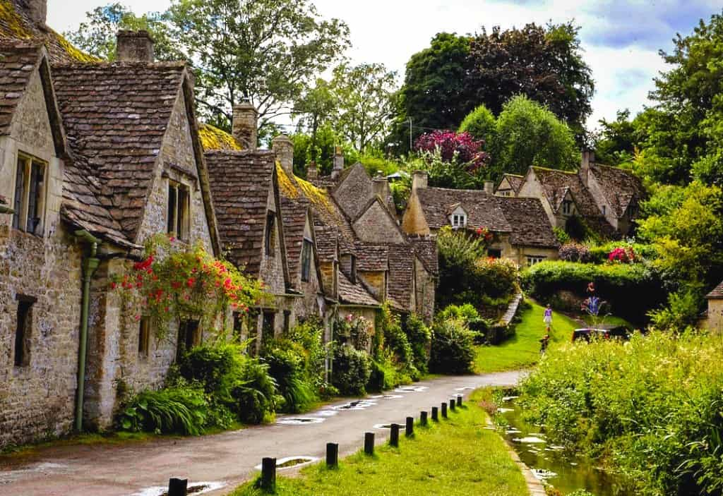 a row of honey coloured stone houses with greenery and trees in english countryside, in bibury a cotswolds village