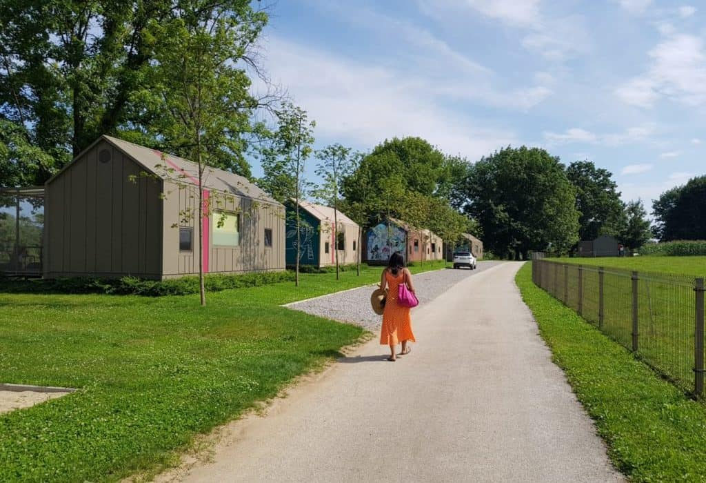 girl in orange dress walks through a green resort with houses on side at big berry in slovenia