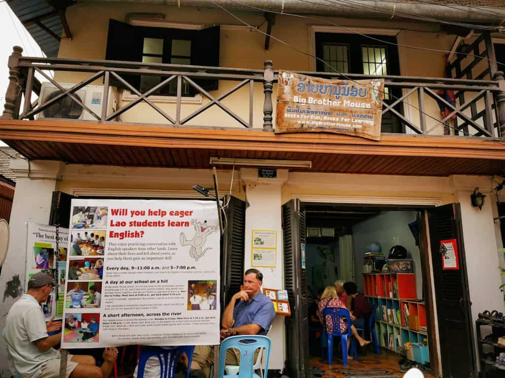 people sitting outside a building in Luang Prabang called big brother mouse a charity helping laos students practise their English with English speakers from all over the world through drop in sessions
