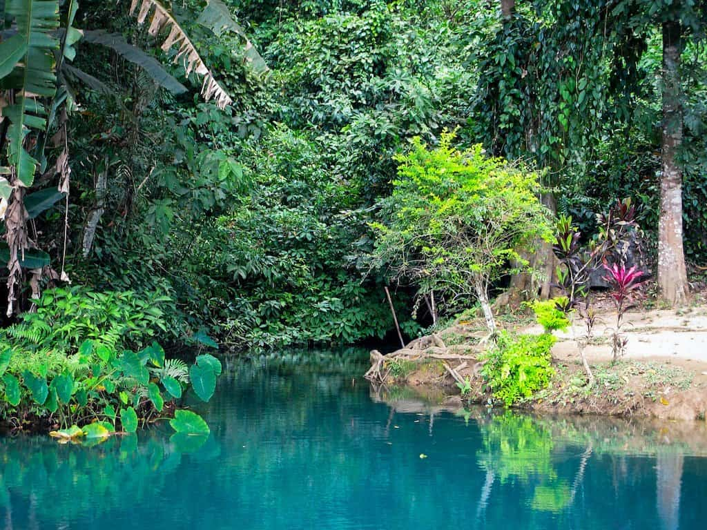 a blue lagoon is surrounded by green trees and jungle in laos Vang Vieng