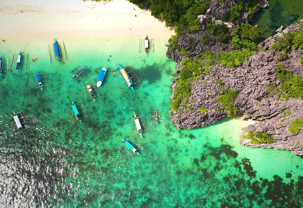 aerial view of islands in caramoan with boats and white beaches, and jagged rocks in the islands